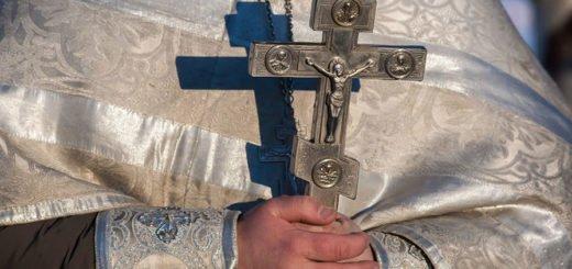 крест в руках священника